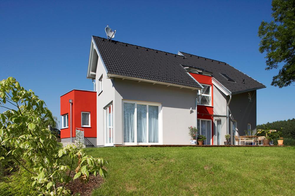 Die Fassade des Satteldachhaus ist in grau gehalten und hat einen nach innen versetzten Verbau, welcher in rotgestrichen ist. Das Satteldach hat ein außergewöhnliche Form, denn die Dachflächen verlaufen asymmetrisch.