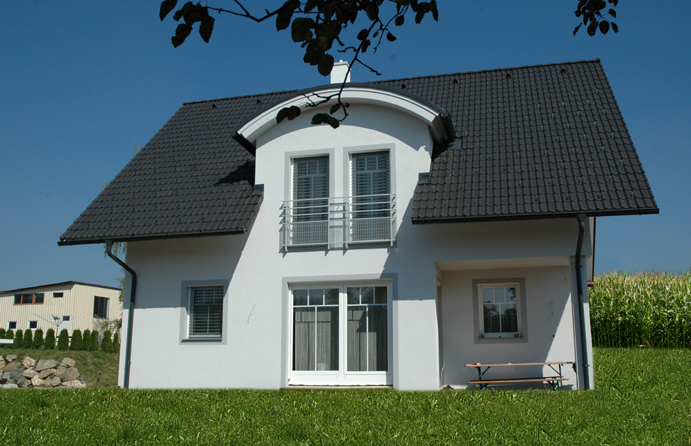 Bei diesem Satteldachhaus zieht sich das Satteldach über das gesamte obere Stockwerk. Es ist mit dunklen Dachziegeln gedeckt. Die Balkontür im Untergeschoss führt in den Garten.