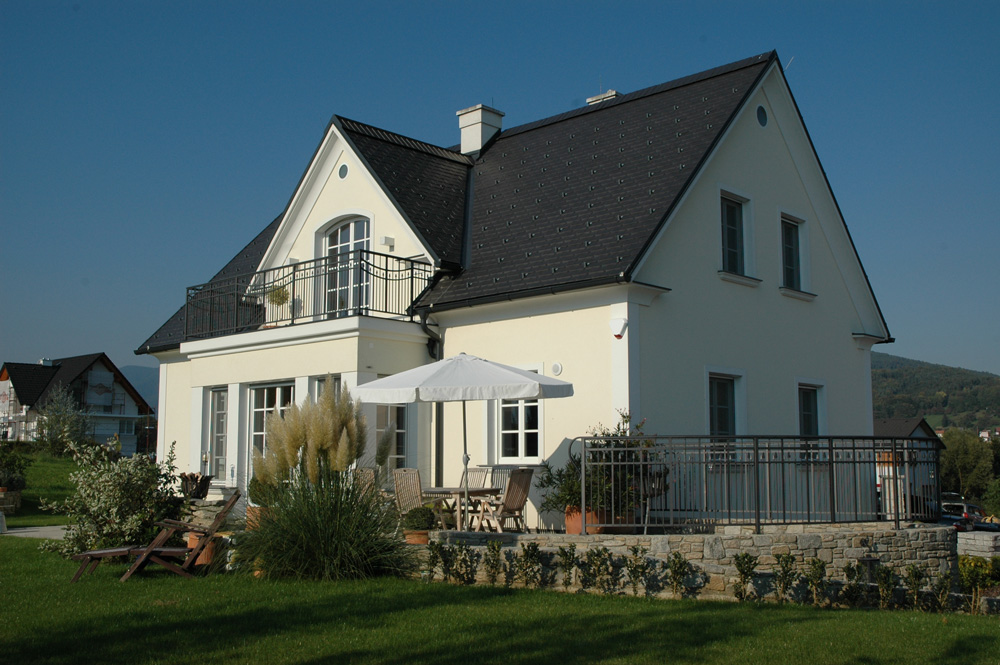 Das Satteldachhaus ist in hellem Gelb gehalten. Im Terrassenbereich befindet sich ein Vorsprung. Auf der Terrasse befinden sich Holzmöbel und ein weißer Sonnenschirm.