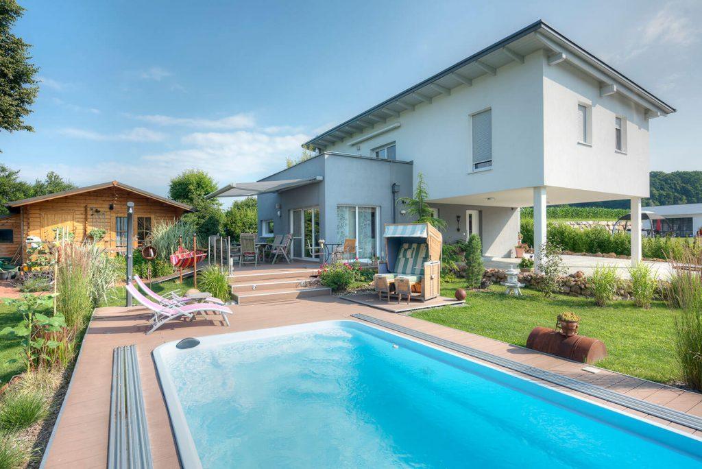 Hier sieht man das Pultdachhaus in Neudau von Lieb Massivhaus mit Garten und Pool.