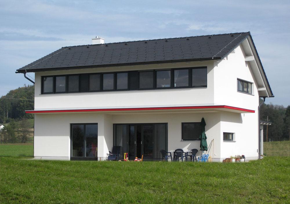 Das Haus zieht sich über zwei Stockwerke. Im Obergeschoss befindet sich eine durchgängige Fensterfläche, welche in Alu eingerahmt ist. Zweischen den Stockwerken wurde ein schmaler Vorbau integriert, der als Überdachung für die Terrasse dient.