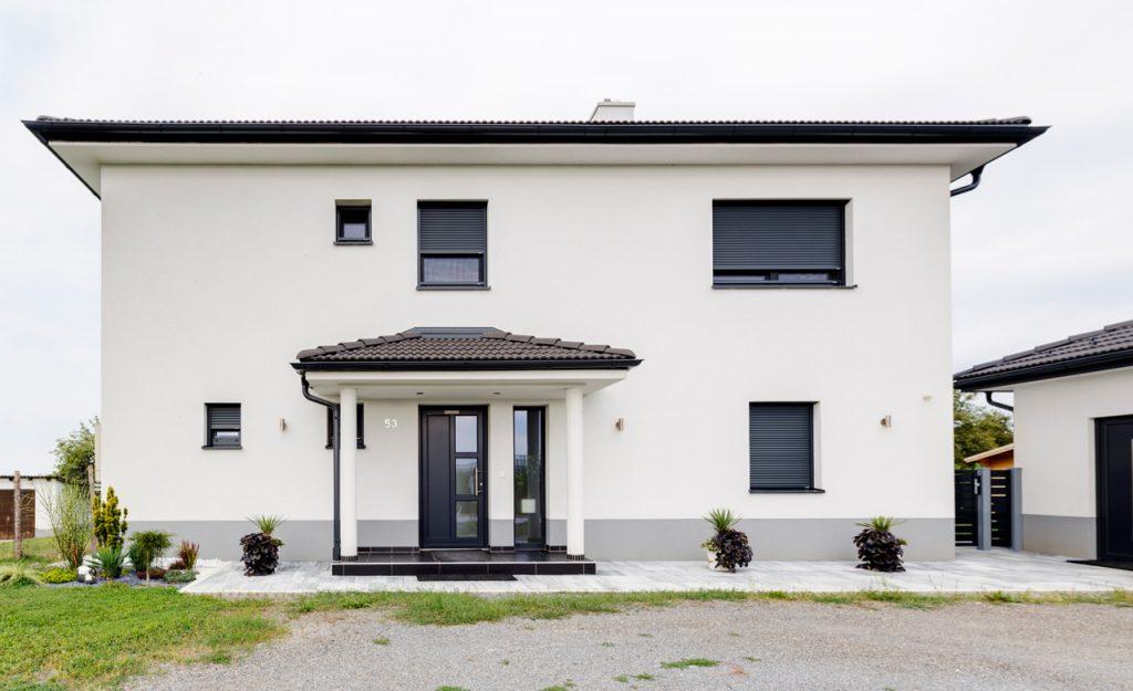 Das Haus mit Walmdach hat eine Fassade in weiß mit einem schwarzen Walmdach sowie schwarzen Alu-Fenstern. Auch die Eingangtüre ist in schwarz gehalten und über ein, mit einem Walmdach überdachten, Podest erreichbar.