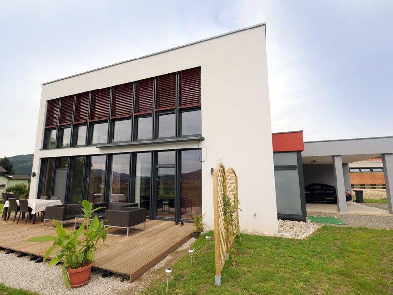 Das Flachdachhaus aus Ziegel hat einen kubisches Form und sehr hohe Wände. Entlang einer Wand befindet sich über die Länge beider Stockwerke Fensterfronten, die mit Alu-Elementen umrahmt sind. Die Jalousien sind aus einem dunklen rot.