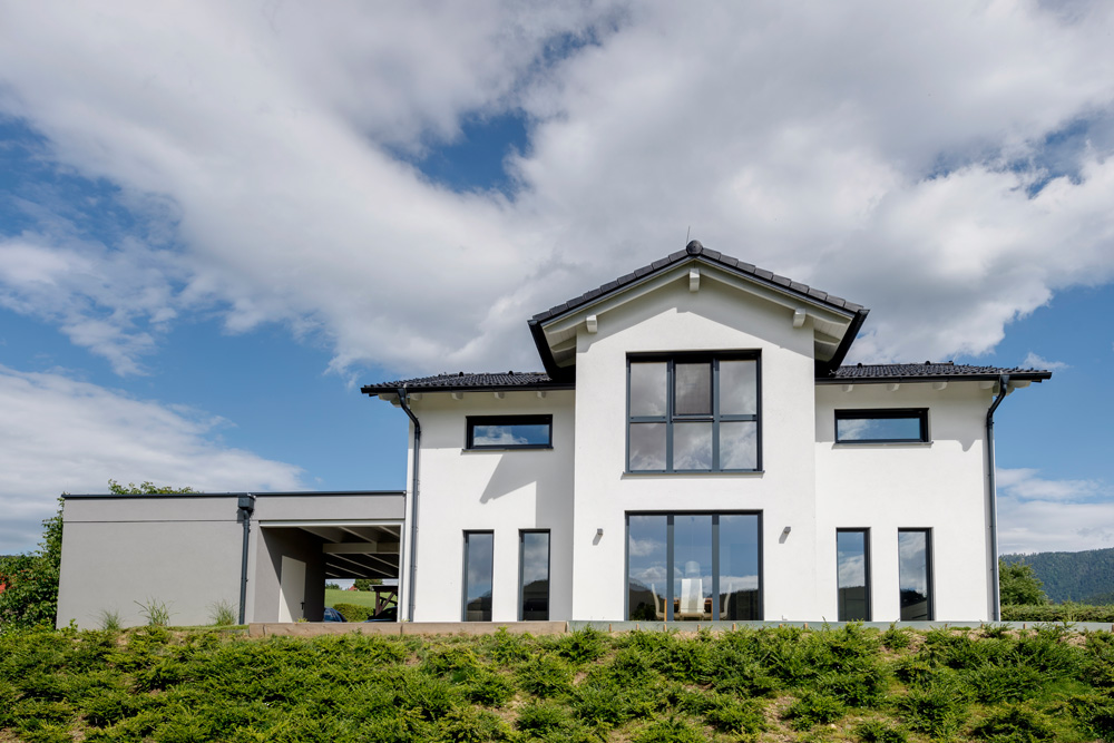 Das Satteldachhaus zieht sich über zwei Stockwerke. Die Fassade des Hauses ist in weiß gehalten. Die anschließende Garage ist in grau.