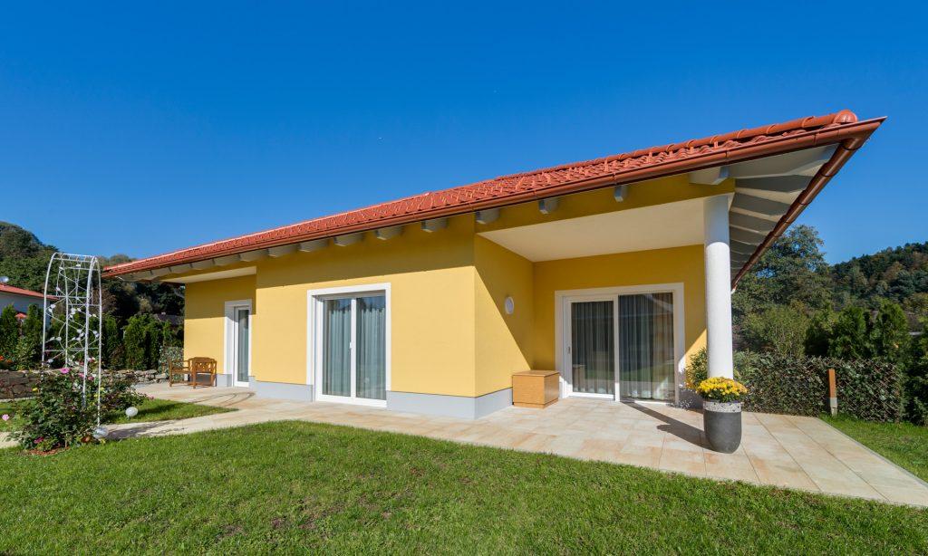 Das kleine Walmdachhaus im Toscana Stil hat Terrasse aus Stein. Im überdachten Bereich der Terrasse wurde das Walmdach mit einer Säule errichtet.