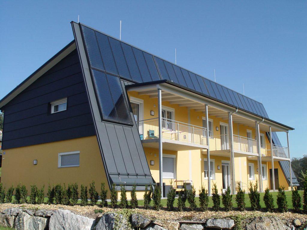 Das Haus hat einen einzigartige Form. Das Untergeschoss ist in gelb gehalten und die Fassade im Obergeschoss ist mit Alu verkleidet und zieht sich auf der Vorderseite bis zum Boden. Auf der Verkleidung befinden sich Sonnenkollektoren.