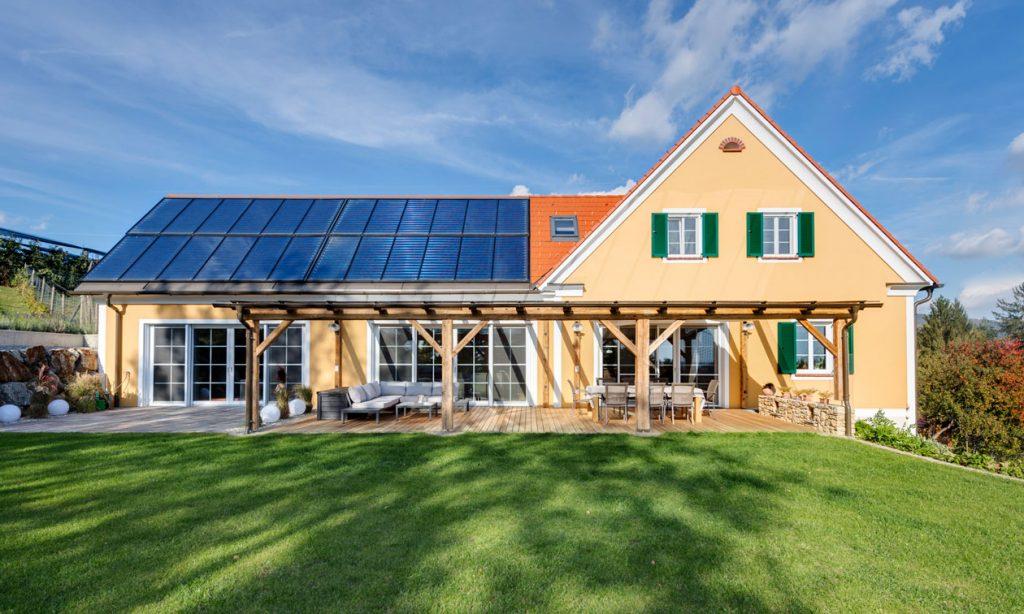 Das Satteldachhaus hat eine gelbe Wandfarbe und Sonnenkollektoren auf dem Dach. Vor dem Haus befindet sich eine großzügige Terasse.