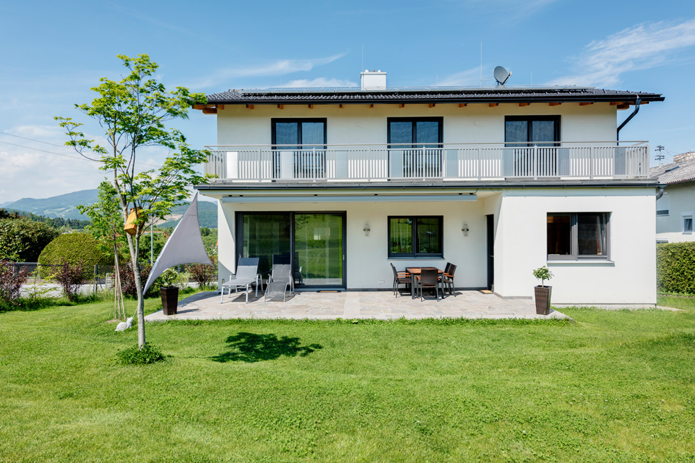 Dieses Satteldachhaus in Fürstenfeld zieht sich über zwei Stockwerke. Über eine Balkontüre kommt man auf die Terrasse mit Steinboden. Über die gesamte Länge des Obergeschosses zieht sich ein Balkon mit Geländer.